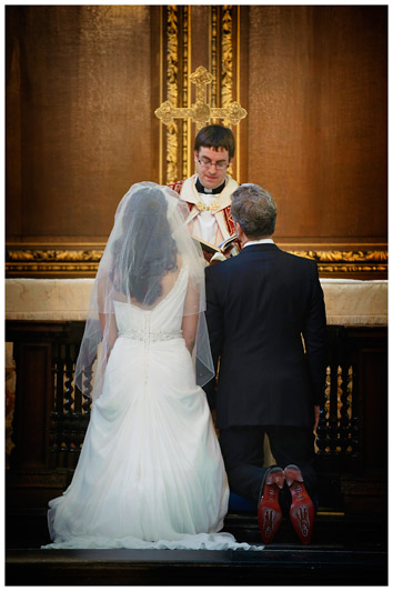 bride and groom kneeling in Christs College Cambridge chapel showing red sole of grooms shoes
