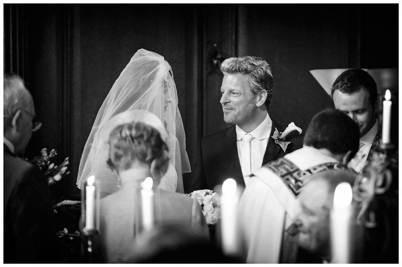 bride and groom exchange look during wedding ceremony at Christs College Cambridge chapel