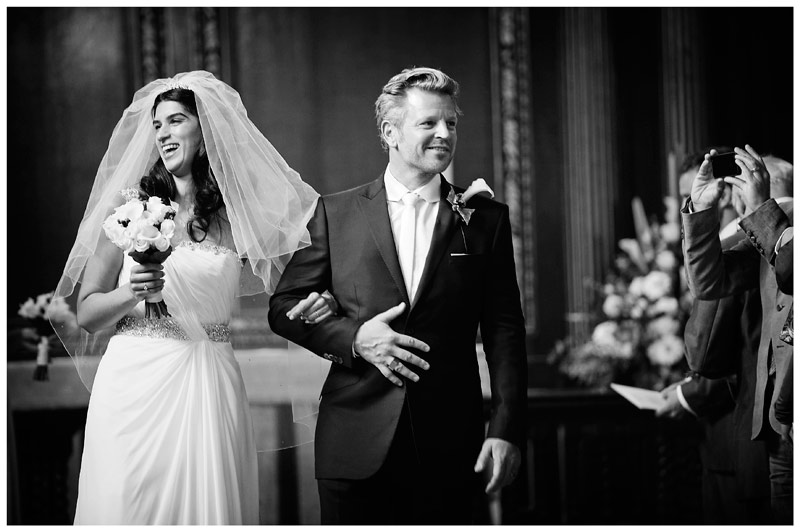 smiling bride and groom walking down aisle of Christs College Cambridge chapel