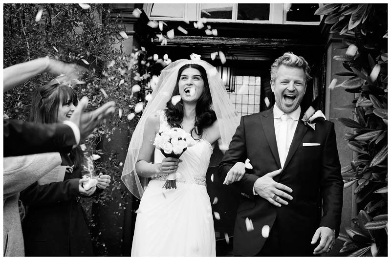 christs college cambridge wedding smiling bride groom during confetti
