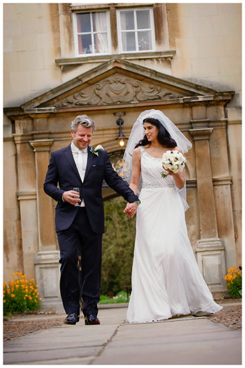 bride and groom walking smiling holding hands in grounds of Christs College Cambridge