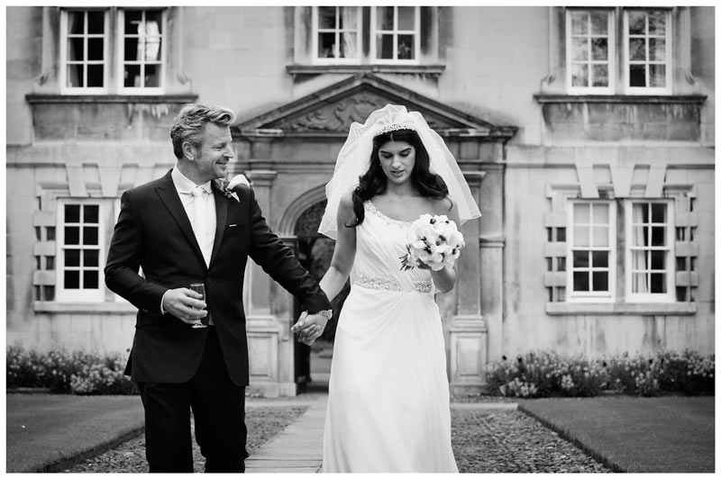 bride groom walking hand in hand in front of Christs College Cambridge college building