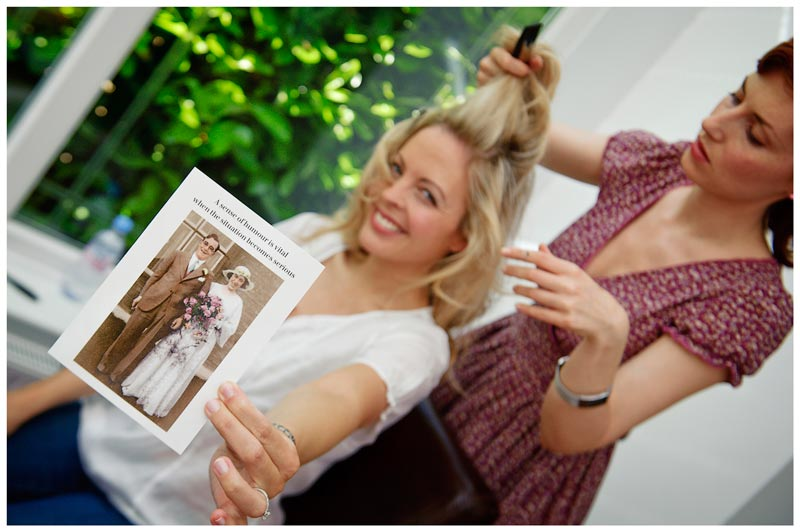 bride holds up a congratulations card while having hair done