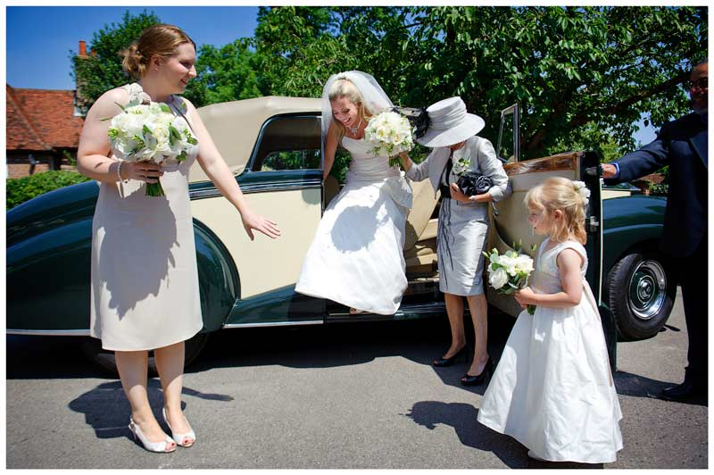 bride getting out of car assisted by mother