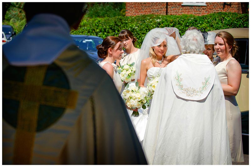 bride lifts veil to talk to vicar