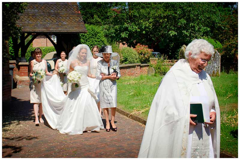bridal party is lead to church by vicar