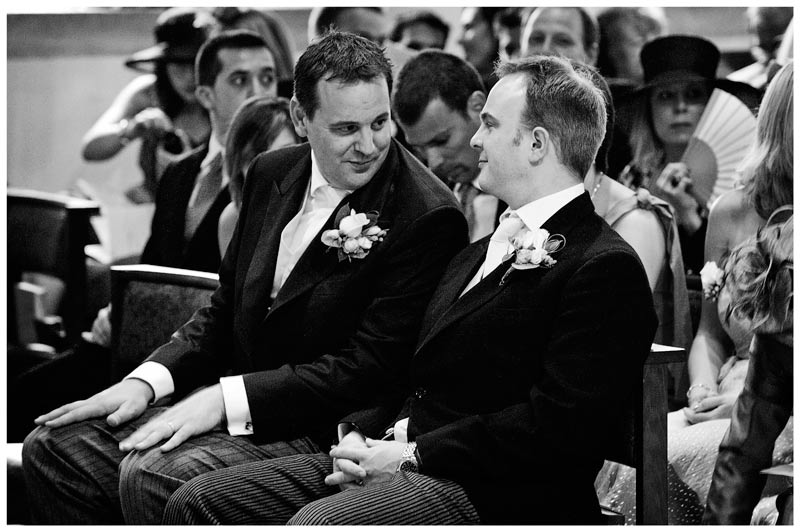 Best man looks at groom as they wait for the bride sitting in Egham Church