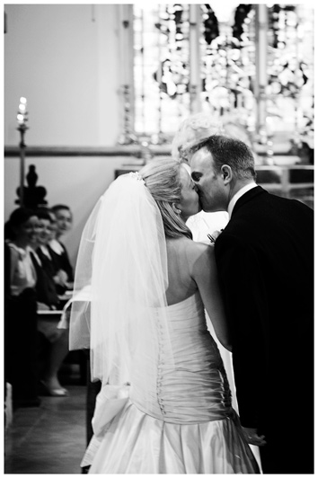 bride and groom kiss at alter of Egham Church