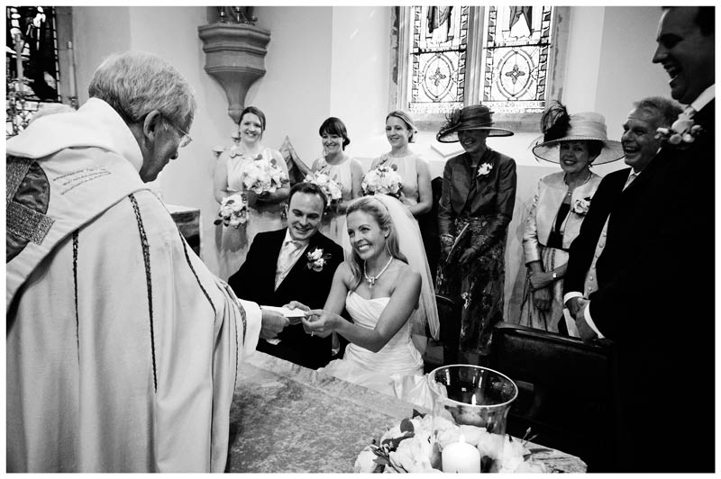 bride and groom receive marriage certificate from vicar