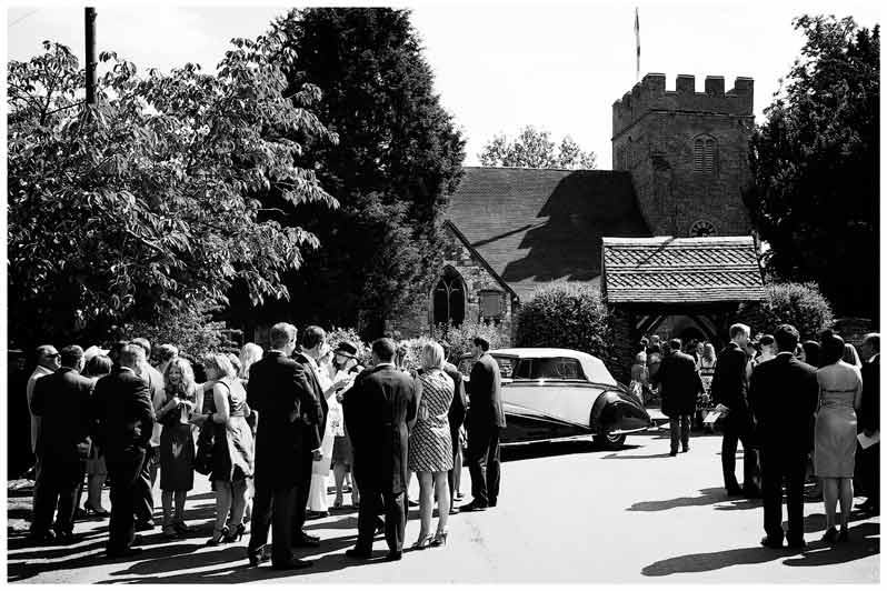 Wedding car and guests outside church
