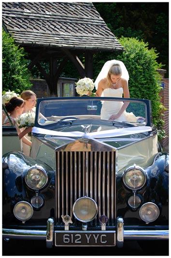 Great Fosters Wedding bride standing up in convertible rollls royce