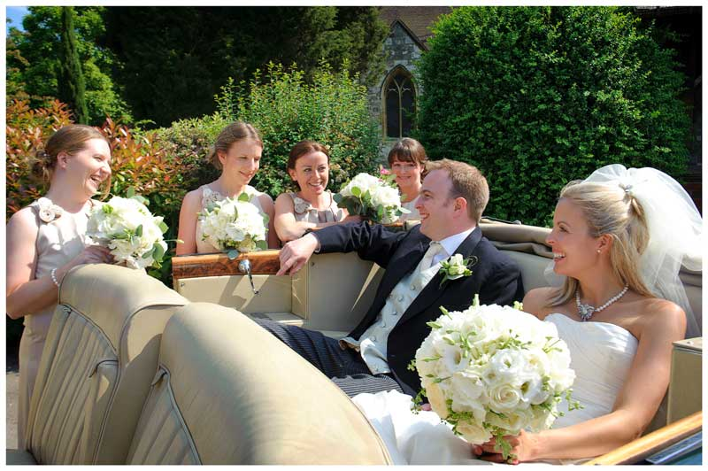 bride and groom in old convertible car talking to bridesmaids