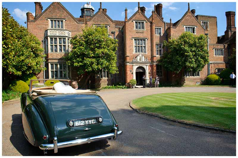 bride and groom arriving at great fosters in rolls royce convertable