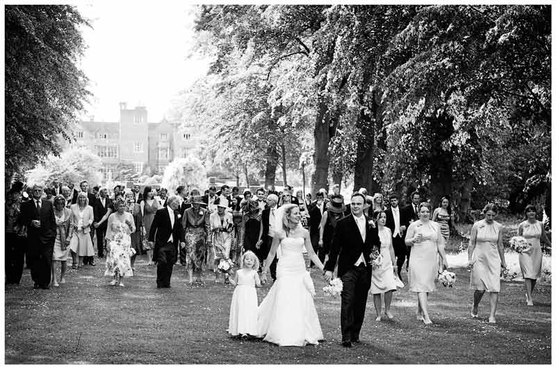 wedding party walking in gardens of in gardens of Great Fosters