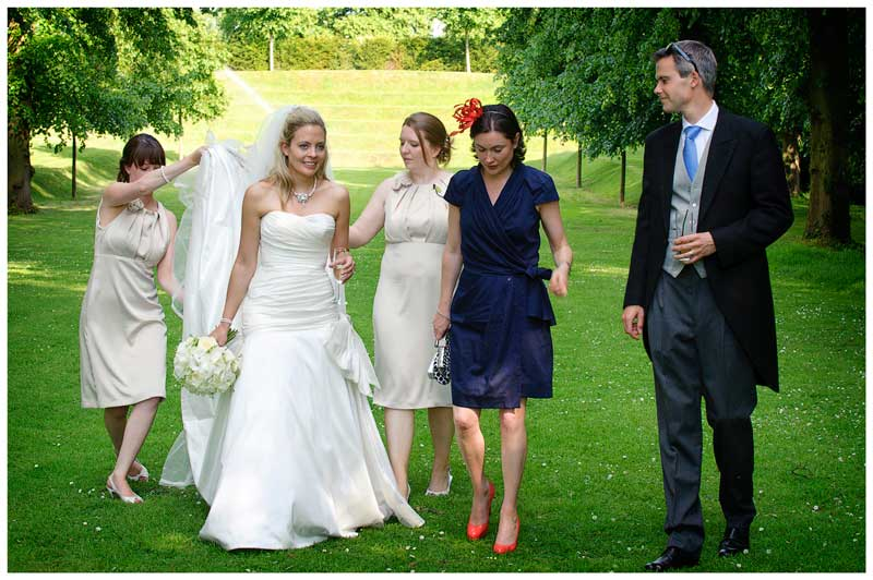 bride and guests walking in gardens of in gardens of Great Fosters