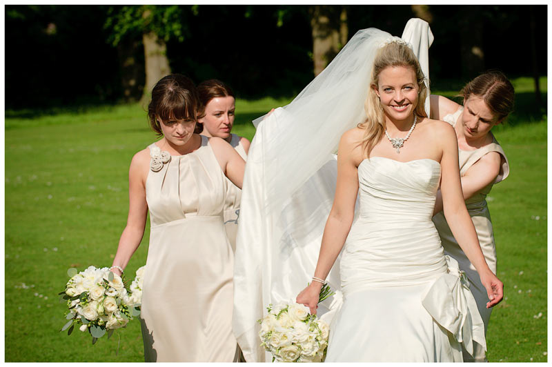Great Fosters Wedding bride walking with bridesmaids lifting brides dress
