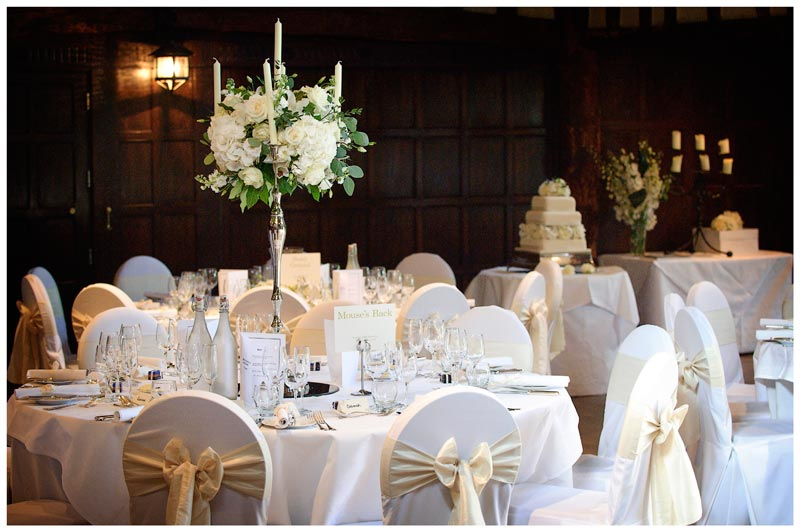 flower table decorations with wedding cake in dining room of in gardens of Great Fosters