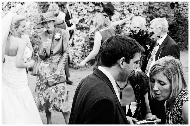 Wedding guests looking at photos bride in background