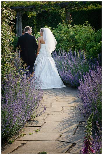 happy couple walking along lavender path in gardens of in gardens of Great Fosters