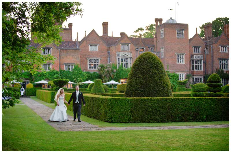 bride and groom walking in garden with Great Fosters behind them