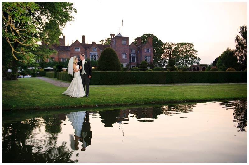 bride and groom embrace standing near water in gardens of Great Fosters