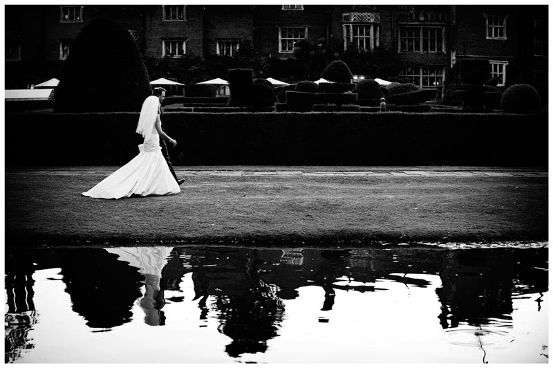 bride and groom walking near water in gardens of Great Fosters