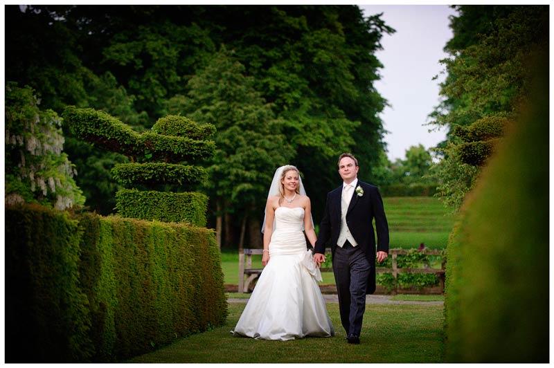 Great Fosters Wedding bride groom holding hands walking in garden Great Fosters