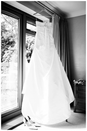 wedding gown hanging from curtain rail
