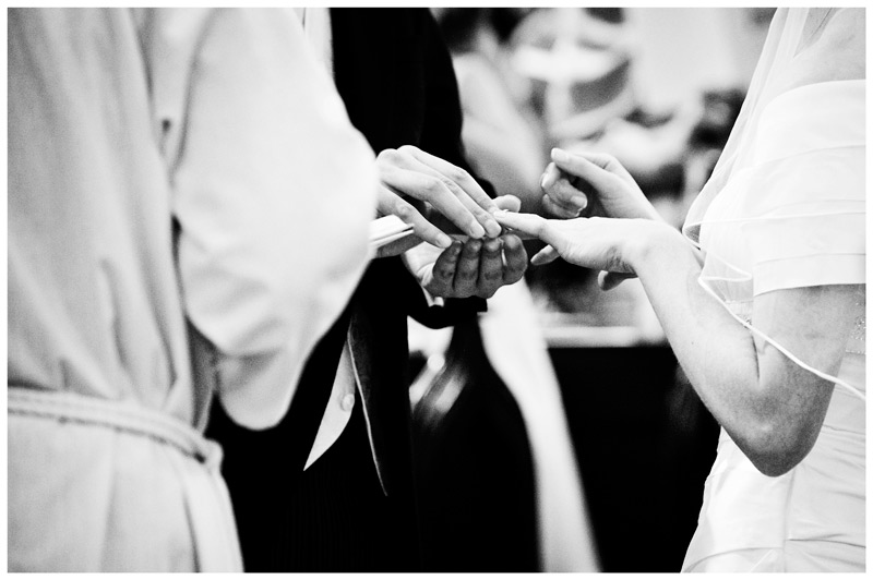 bride shows where groom should place wedding band on her finger