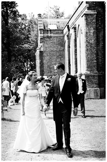 bride groom walking away from church hand in hand