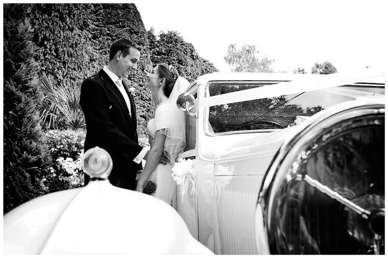 bride groom standing next to car