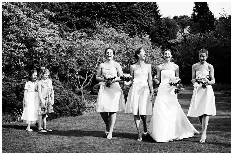 brides bridemaids walking watched by two little girls in gardens of Jermyn's House