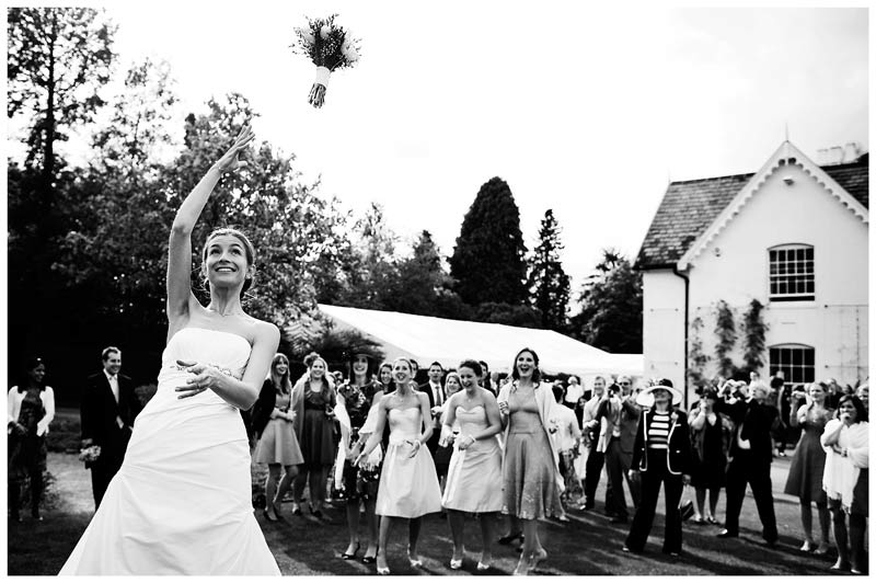 bride throws bouquet in gardens of Jermyn's House