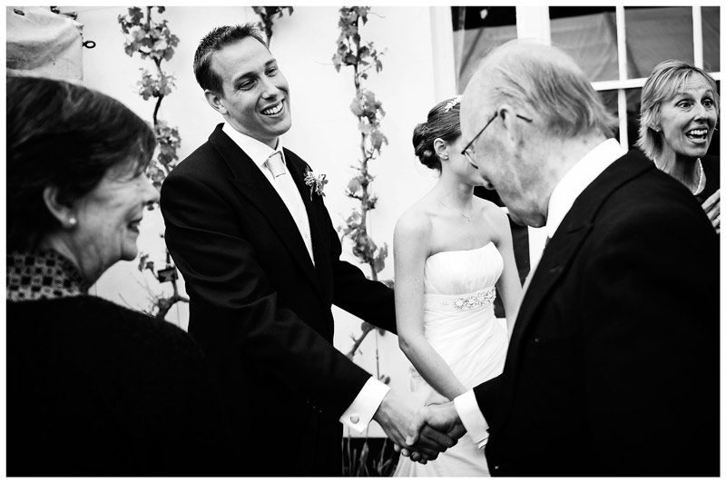 groom shaking hands old gentleman