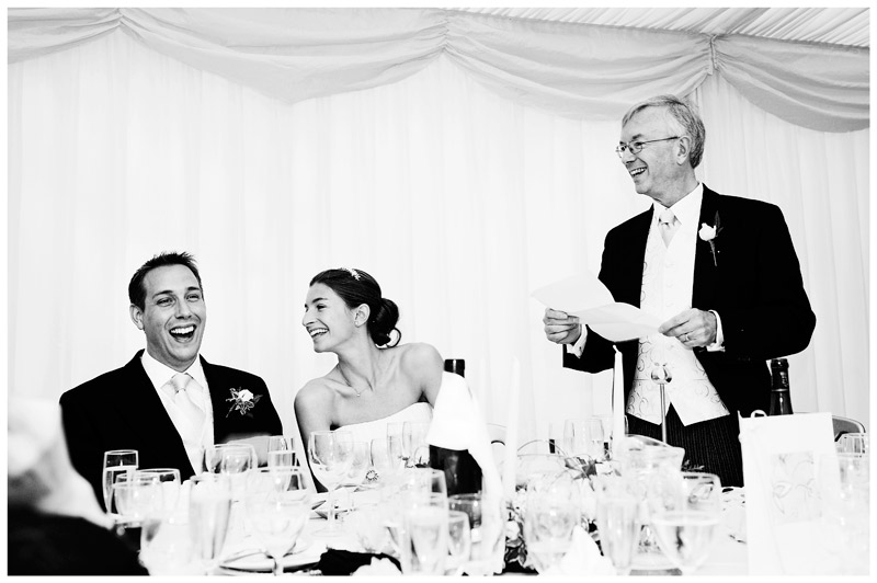 laughing bride and groom during fathers speech