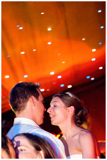 bride sings to groom as they dance against orange light