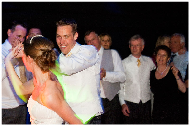 groom smiles at bride as they dance as guests watch in marquee at Jermyn's House