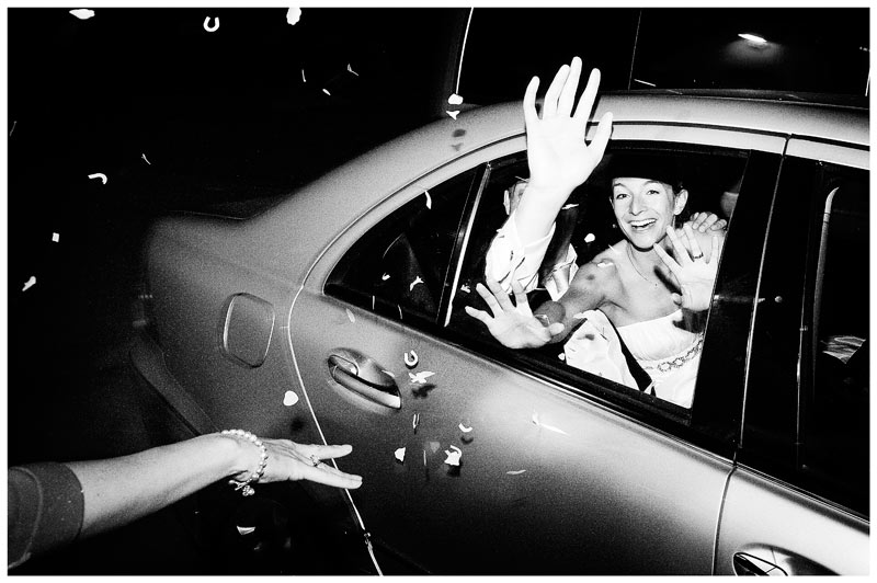 happy couple waving from car window as they leave Jermyn's house wedding reception
