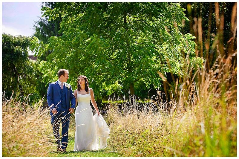 Bride and groom walking in grounds madingley hall