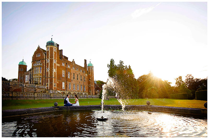 bride groom sitting on madingley hall fountain in th eevening