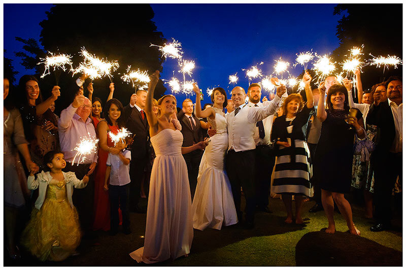 wedding party waving sparklers at night at chippenham park