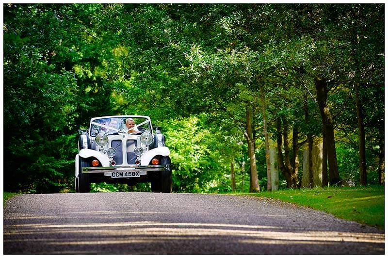 bride and groom arrive at longstowe hall in their wedding car