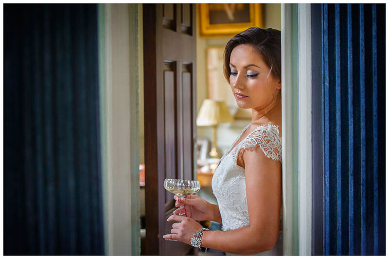 bride hold champagne glass between two blue pillars