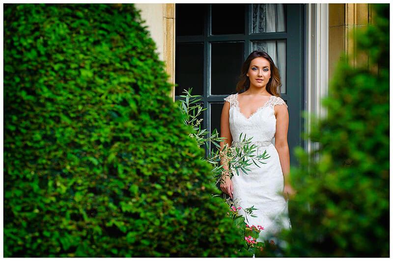 bride in doorway between two privet bushes