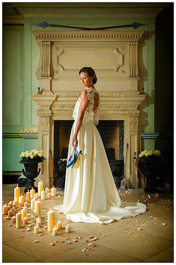 bride surrounded by candles holding shoes