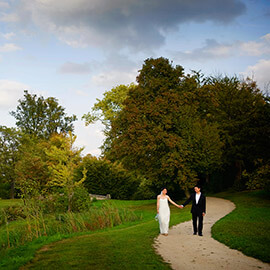 bride groom walking holding hands in Palace Versailles Gardens