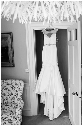 brides dress hanging in door way