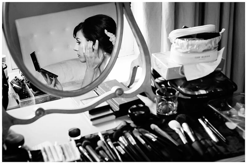 bride checks her make up during bridal preparations