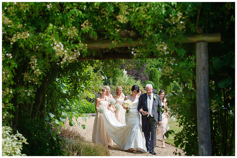 bridal party walking to ceremony in chippenham park gardens