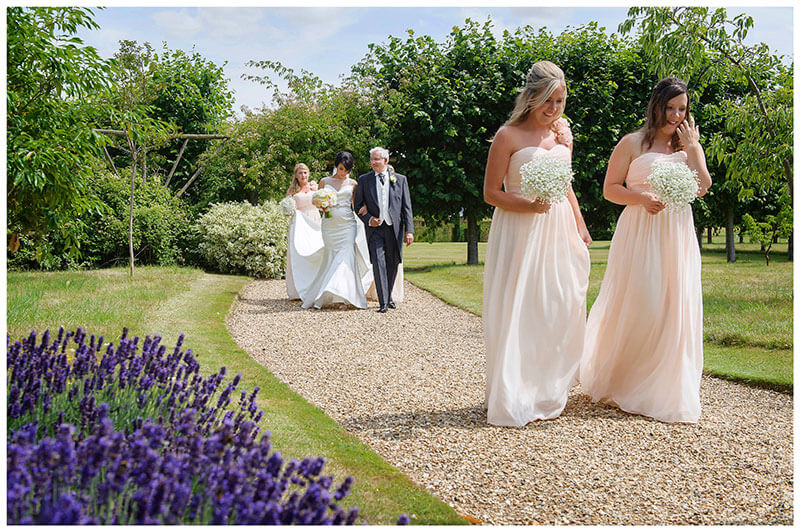 bridal party walking along lavender foot path in chippenham park gardens